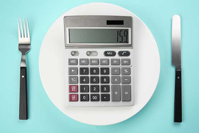 Calculator On a Plate With Knife and Fork Representing Counting Calories.
