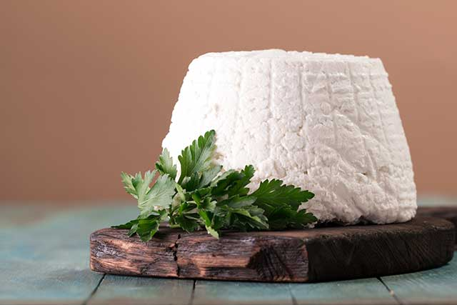 Fresh Ricotta Cheese On a Wooden Board.