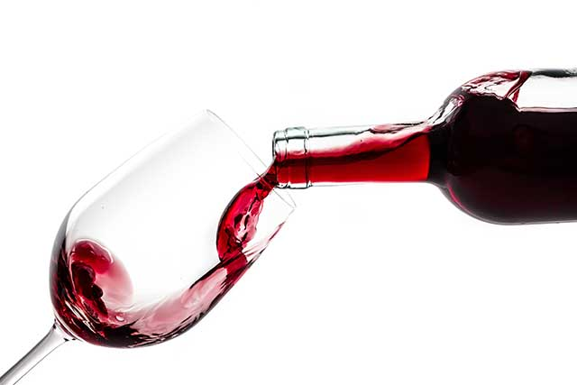 Pouring Red Wine From a Bottle Into a Glass.