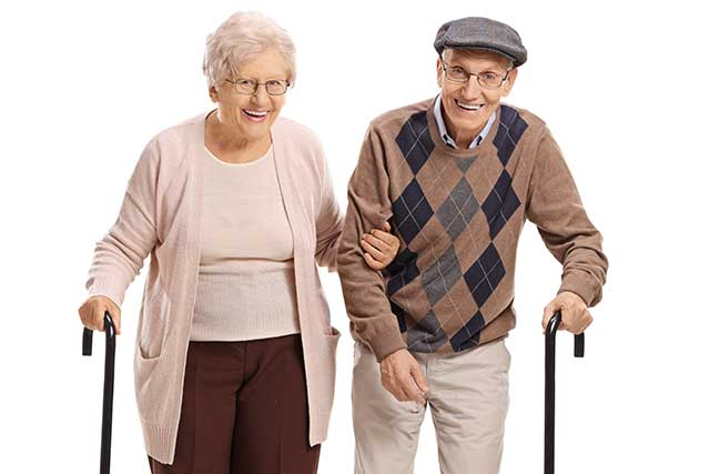 A Smiling Elderly Couple Walking Arm In Arm.