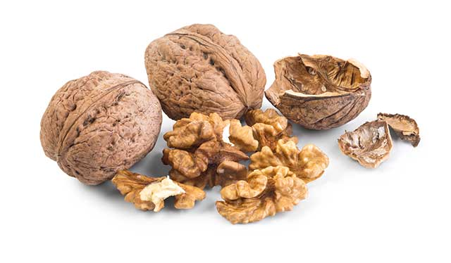 Whole and Shelled Walnuts Next To Each Other.