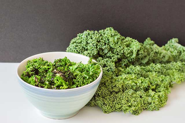 A Bowl of Kale Chips and Leaves of Fresh Kale.