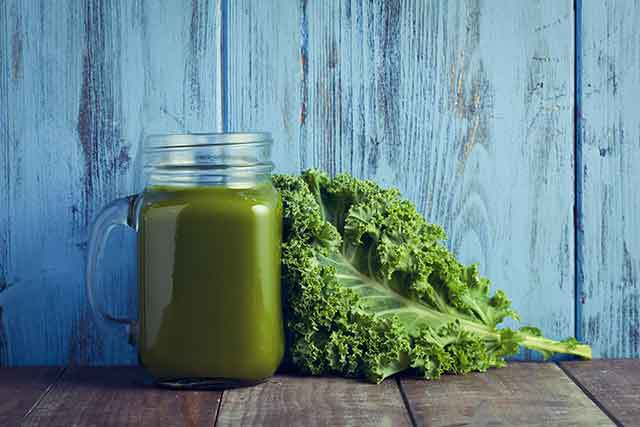 Kale Smoothie In a Glass Jar Next To Fresh Leaves.