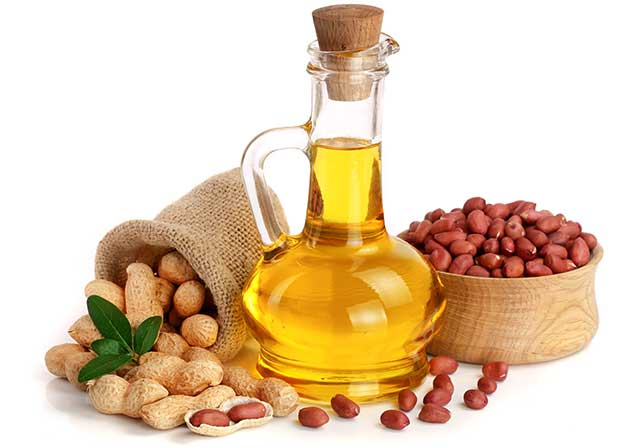 Peanut Oil In a Glass Bottle Next To Bowl of Peanuts.