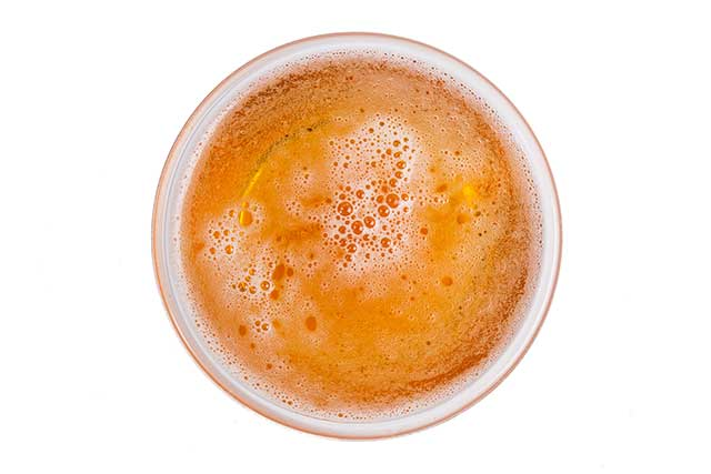 A Topdown View of a Beer Glass Showing Foam On Top.