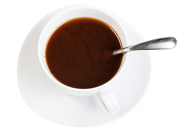 Black Coffee In White Mug On a White Saucer With Teaspoon.