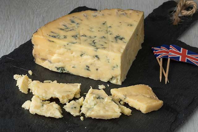 Blue Stilton On Cheese Board Next To Small British Flags.