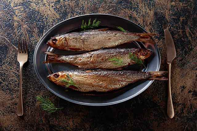 Three Grilled Herring Fillets On a Plate.