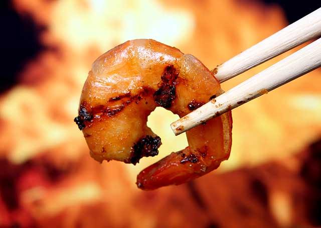 Holding King Tiger Prawn Shrimp With Wooden Chopsticks.
