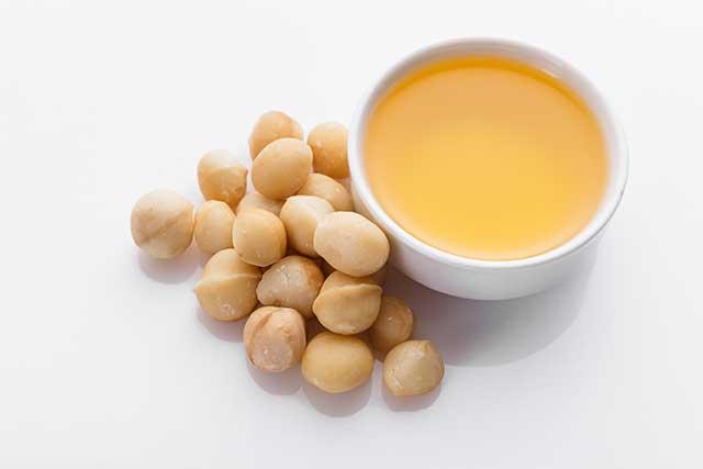 Macadamia Oil Next To Macadamia Nuts.