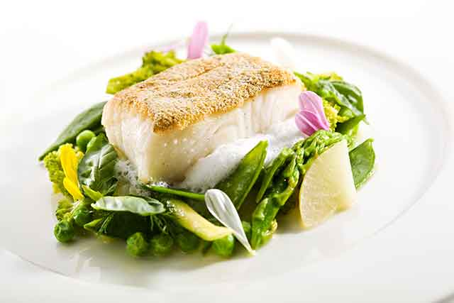 Thick White Halibut Fish Steak On a Plate With Vegetables.