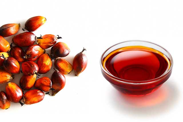 Red Palm Fruit Next To a Glass Bowl of Red Palm Oil.