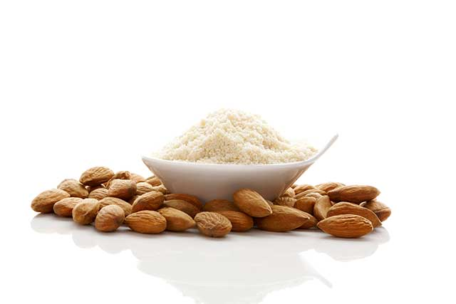 Bowl of Almond Flour Next To Pile of Whole Almond Nuts.