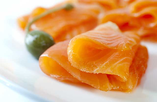 Cold-smoked Salmon Slices On a White Plate Next To Caper Berry.