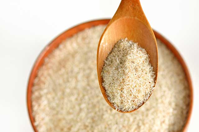 Ground Psyllium Husk In a Wooden Bowl and On Wooden Spoon.