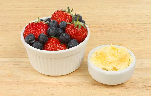 Clotted Cream and Mixed Berries In Separate Small Bowls.