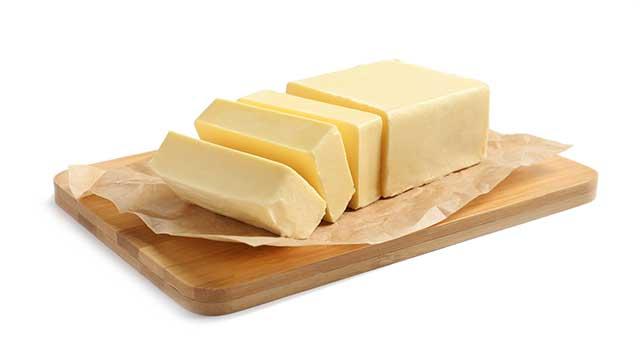 Block of Cut Butter On a Wooden Chopping Board.