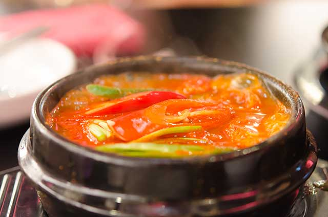 Kimchi Jjigae (Kimchi Stew) In a Black Ceramic Bowl.