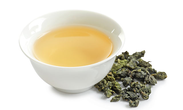 Oolong Tea In a White Cup Next To Tea Leaves,