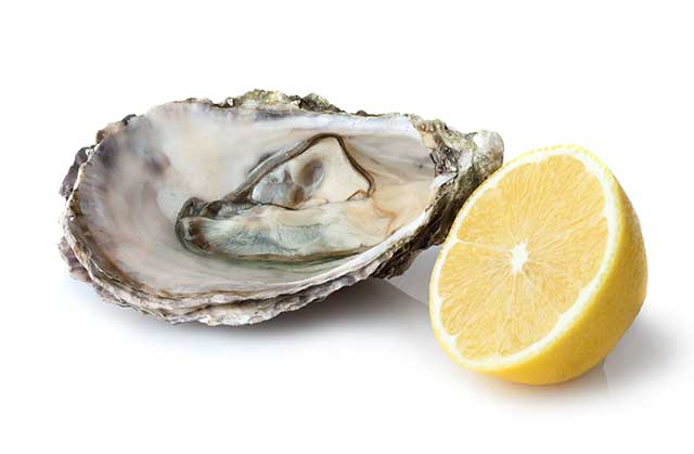Open Shell Oyster Next To Lemon Juice.
