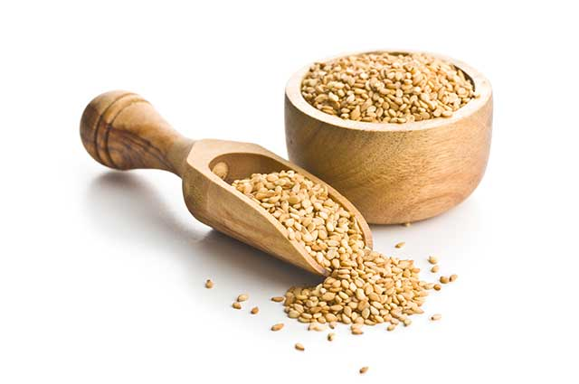 Sesame Seeds In a Wooden Bowl With a Wooden Scoop.