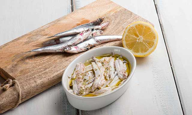 Whole Anchovies and Marinated Anchovy Fillets In White Bowl.
