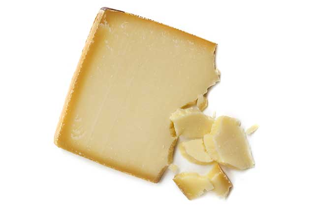 Close-up Image of Gruyere Cheese Block and Crumbly Pieces.