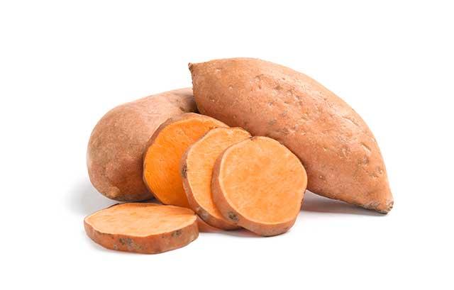 Fresh Sliced Sweet Potatoes and Two Whole Sweet Potatoes.