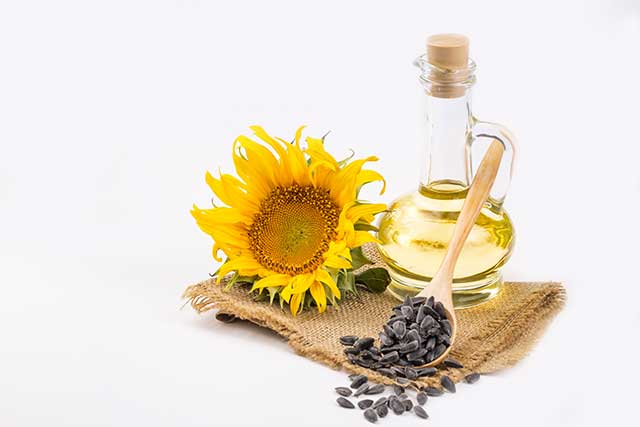 Glass Bottle of Sunflower Oil Next To Flower and Seeds.