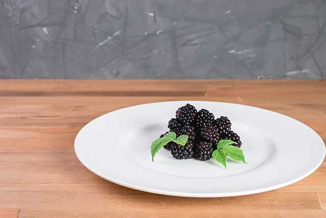 Pile of Boysenberries On a White Plate.