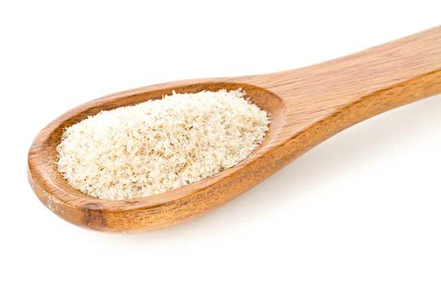Psyllium Husk Powder On a Large Wooden Spoon.