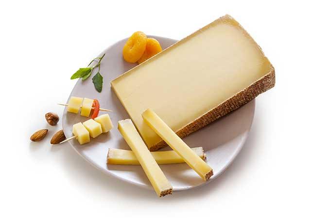 Swiss Gruyere Raw Cheese On a White Plate.