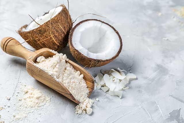 Coconut Flour Next To Two Coconut Halves.