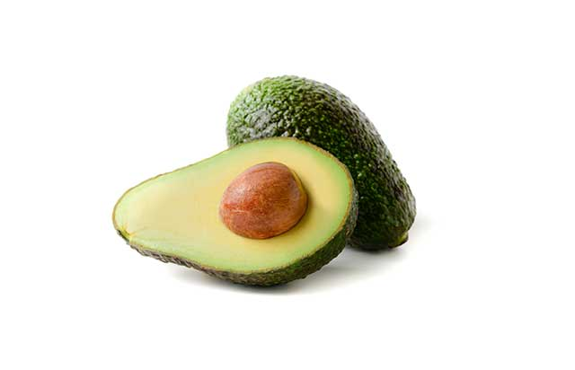 Half an Avocado With a Whole Hass Avocado Behind It.