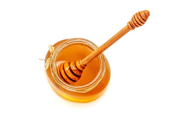 Honey Dipper In Jar of Sticky Honey.