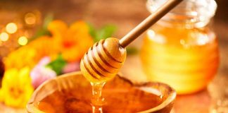Thick and Sticky Honey In a Bowl With Honey Dipper.