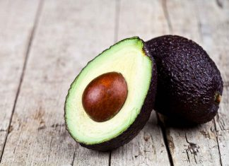 Whole and Half Avocado On a Wooden Surface.