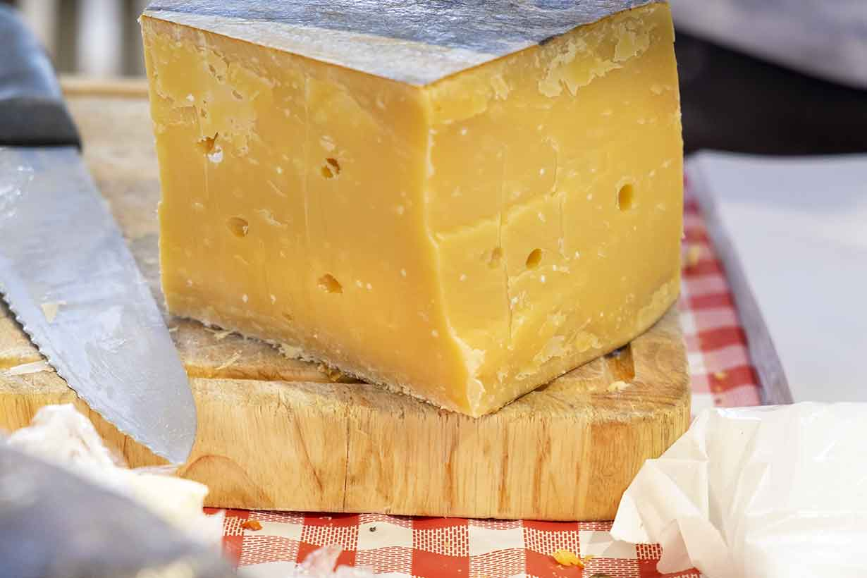 Aged Vintage Gouda Cheese On a Wooden Board.
