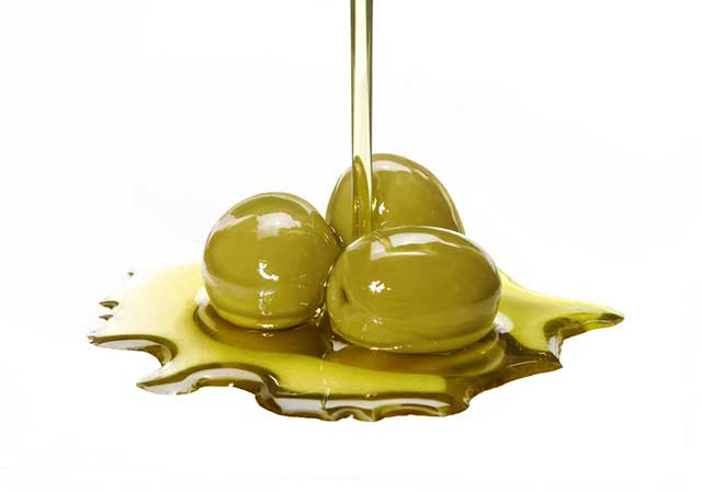 Extra Virgin Olive Oil Being Poured On Green Olives.