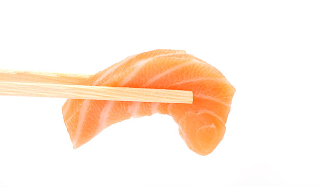 A Piece of Salmon Sashimi Held In Two Chopsticks.