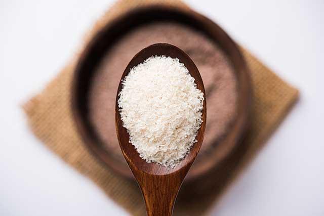 Psyllium Husk Fiber Supplement On a Wooden Spoon.