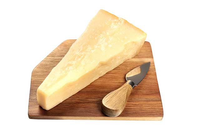 Aged Parmesan Cheese On a Wooden Chopping Board.