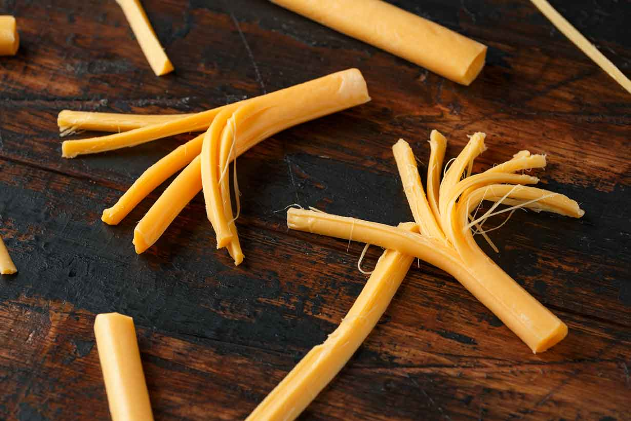 Sticks of String Cheese On a Wooden Surface.