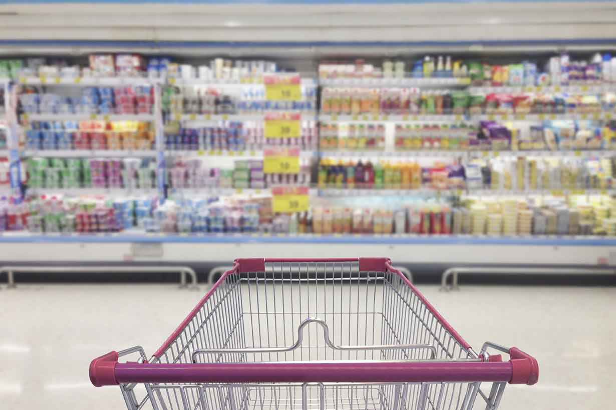 A Trolley In Front of Processed Foods In a Supermarket.