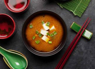 Traditional Miso Soup In a Bowl With Spoon and Chopsticks.