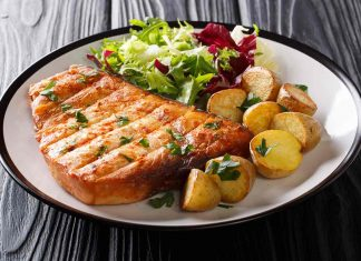 A Thick Cut of Swordfish Served With Salad and Potatoes.