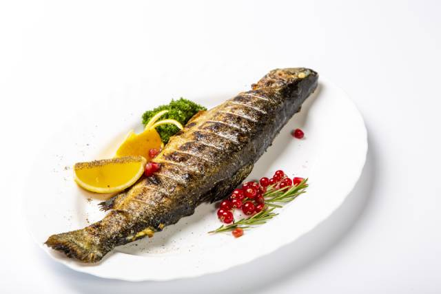 Grilled Trout On a Plate With Lemon Slice and Herbs.