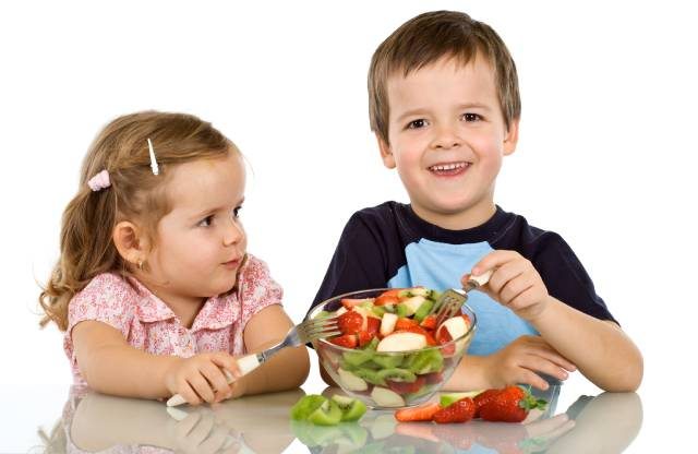 Boy and Girl Eating Fruit From a Fruit Bowl.
