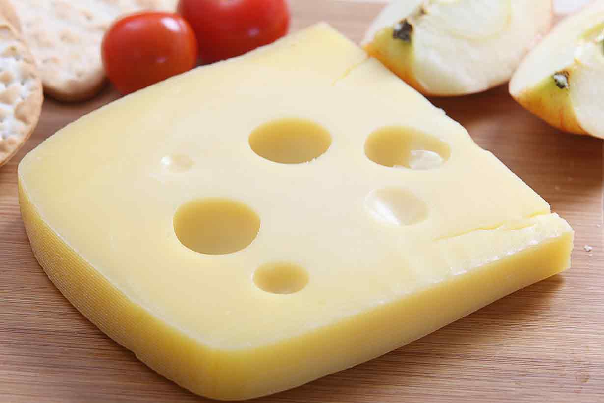 Piece of Jarlsberg cheese with characteristic holes.