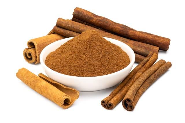 Ground Cinnamon and Cinnamon Bark Alongside Each Other.